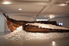 Cai Guo-Qiang - The site-specific installation entitled Reflection consists of a 50-foot-long skeleton of a sunken Japanese fishing boat resting upon an imaginary beach of gleaming broken white blanc de chine porcelain fragments of deities from Dehua, China