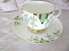 """Description: This set features an Art Deco design in colors of green, blue, black, and gold. The foot of the cup is trimmed in gold.  Dimensions: The cup is 2 ¾ inches tall and 3 inches wide at the rim. The saucer is 5 ½ inches in diameter.  Materials: Porcelain  Age: The back stamp reads """"Plant Tuscan China England,"""" dating the set to about 1936. Condition: Excellent. There are no chips, cracks, areas of crazing or repairs. The design and gold trim are intact."""