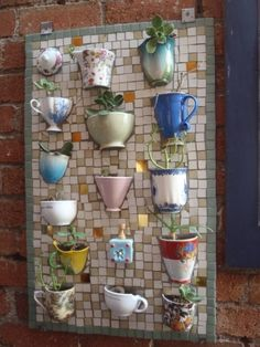 A mosaic board done with half-teacups and coffee mugs to plant succulents and/or herbs. A unique garden feature.