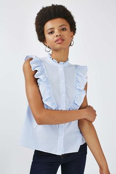 In a soft blue hue, this sleeveless ruffle stripe shirt is a dream. Constrast with a dark frayed jean for a modern yet feminine look. Ruffle Shirt, Sleeveless Shirt, Ruffle Top, Crop Top Outfits, Jean Outfits, Light Blue Shirts, Flutter Sleeve Top, Summer Blouses, Glamour
