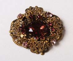 Vintage brass filigree brooch with rpurple glass rhinestones
