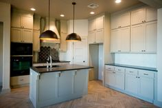 Custom kitchen in Regency Pointe with gray cabinets, dome pendants, and wood-look tile in a herringbone pattern