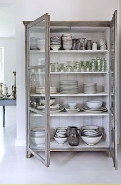 Natural Glass-Front Cabinet - used to store and display collected dishes. This beautiful all-white home is in Denmark - via Blanc Nordique