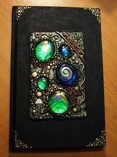 """Hand painted blank book decorated with polymer clay in various colors, iridescent glass gems in aqua and green and a bit of silver jewelry. Painted with acrylic and metallic paints. The book measures 5.75"""" x 8.75"""" and has 100 pages that are lined on one side and the other is blank for sketching and such. I placed foil behind each gem and the light bounces off the mirrored surface and causes the gems to glow. It's a really cool effect!"""