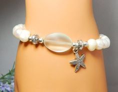 This ocean inspired bracelet is made with a Seafoam Sea Glass focal bead surrounded Freshwater Pearls with a Silver Starfish Charm. Simple and Beautiful. Freshwater Pearl Properties: Are calming and c