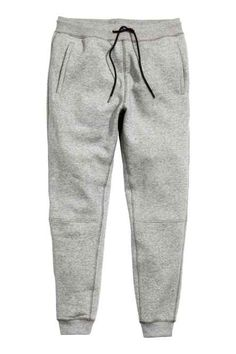 Sweatpants with an elasticized drawstring waistband, dropped gusset, side  pockets, and one back pocket. Tapered legs with seams at knees and
