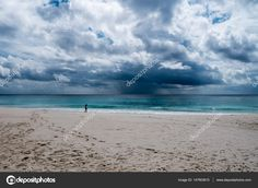 Woman walking alone on a tropical beach while a storm is coming