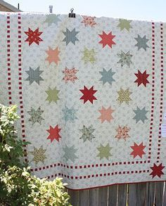 sawtooth star.  One way to make this is with groups of stars in compatible colors.  They don't need to all be the same color.  also note in this quilt alternating plain squares.