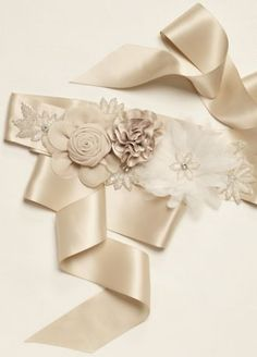 This silky sash will be the perfect splash of champagne to compliment your bridal look!  Sash features a beautiful array of flowers in different sizes using several materials and adorned with sparkling stones.  Measurements: 2 inchesby 108 inches.  Available in champagne.  Imported.