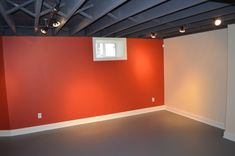 Tip for finishing basements - To make ceiling feel higher and still have a finished look, paint the framing. A dark color works especially well for this because it helps the ceiling look like it recedes.