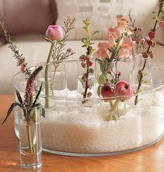 Un original centro de flores. Reparte flores y ramas pequeñas de peonías, verónicas y ranúnculos en vasitos de licor. Mételos en un centro grande de crital no muy algo y relleno de sal gorda