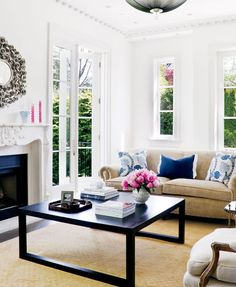 chic living room | tan couches + jute rug + black coffee table + white walls