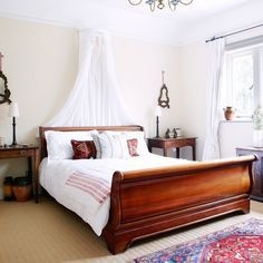 Vintage Bedroom: A charming cherry wood sleigh bed, dressed with French linens, sits between two vintage bedside tables. Photo Credit: house to home