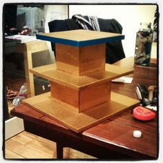 Homemade cupcake stand. Used 3 cake boards, cut them to different sizes and glued 4 pieces of balsa wood on 2 layers to make them stackable. Spray paint gold & edge with ribbon.
