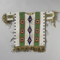 A LAKOTA BEADED AND FRINGED HIDE CHILD'S SHIRT    composed of hide, glass beads, and sinew.  Length with fringe 20 in.