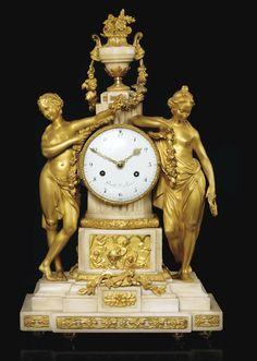 Pendule en marbre blanc et bronze doré d'époque Louis XVI, le cadran et le mouvement signé GAVELLE L'AINE PARIS, le cadran au centre d'une colonne cannelée flanquée de deux femmes drapées tenant une guirlande de fleurs et une couronne de laurier, sommée d'un vase de forme antique garni de fleurs, reposant sur une base à décor de bas-reliefs de trophées musicaux et allégorie des sciences en bronze doré, sur un socle à décor de rosettes et frise d'entrelacs.