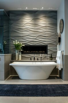 Contemporary- Typical design features in this space include the large geometric shapes on the walls and the square edge tub and open feel in the bathroom.