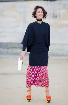 Yasmin Sewell in a black top, printed skirt, and platforms