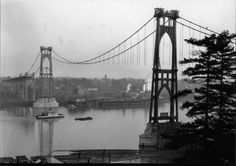 """St. Johns Bridge during construction 1930A spectacular 1930 image of the St. Johns Bridge during construction. The main cables and suspender cables are in place waiting for the deck to be hung. """"Cables Manufactured and Erected by Roebling"""" refers to the John A. Roebling's Sons Company, whose founder designed the Brooklyn Bridge. In the distance, below the center cable span, you can see the old vernon standpipe which was moved from Northeast Portland in 1920."""