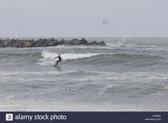 Download this stock image: Surfing in a cloudy day. - HHE5B4 from Alamy's library of millions of high resolution stock photos, illustrations and vectors.