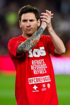Lionel Messi of FC Barcelona applauds the crowd wearing a shirt in support of Syrian refugees prior to the La Liga match between FC Barcelona and Levante UD at Camp Nou on September 20, 2015 in Barcelona, Catalonia.