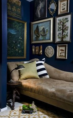 I love this!! Dark blue walls decorated withcool framed art with a cozy reading spot. Maybe not for this room, but for some dream room...