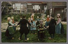 Groep kinderen in Marker dracht aan het spelen in een kring. Marker houten huizen op de achtergrond. 1900-1907 #NoordHolland #Marken