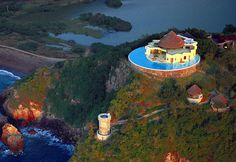 "WOW - Costa Careyes, Mexico, lies between Manzanillo and Puerto Vallarta. The Costa Careyes resort boasts villas known as ""The Castles of Careyes."" Sol de Oriente, pictured, is a villa with six bedrooms encircled by a giant infinity pool. Swimmers can simply step outside of their rooms, plunge into the water, and take delight in a view that stretches to the great blue Pacific Ocean."