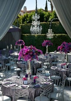 Decoración de mesas en gris, fucsia y plateado. Los centros de mesa se destacan y contrastan con el verde del jardín.