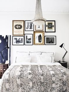 Elegant bedroom with white bedding, a chandelier, and a gallery wall