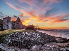 We love this image of the sun setting over Lochranza Castle on Arran #Scotland