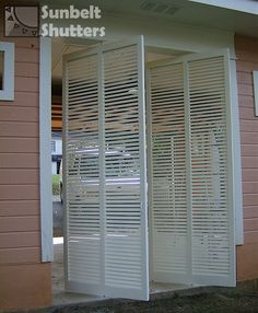 Bahamas shutters are used here as revolving doors on a carport.  Notice the pins above and below their center mullions that allow them to rotate open.