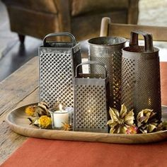 Old cheese graters over tealights. Cheese graters as vases? Would go with cheeseboard/food theme if we decide on that. KL