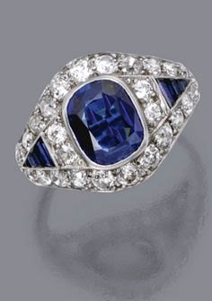 SAPPHIRE AND DIAMOND RING, CIRCA 1930 The cushion-shaped sapphire weighing 3.33 carats, flanked by calibré-cut sapphires in triangular motifs, within borders of old European-cut and single-cut diamonds, mounted in platinum, size 8¾.