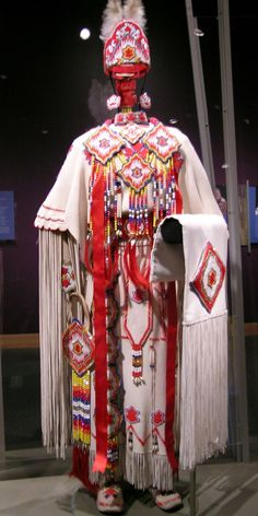 Kiowa Three-Hide Dress    Modern Kiowa three hide dress and high top moccasins, Comanche crown and other accessories. 1994, Oklahoma.  Dress made of hide, seed beads, ribbon, cotton, rawhide and thread. This dress was made for the owner's wedding when she married a Kiowa man. It was made by his mother following traditional Kiowa way with patterns handed down from her grandmother. This follows a plains tradition of dressing their new relative in clothing representative of their family.