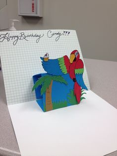 Pop-up parrot birthday card holding a cupcake
