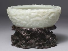 An Imperial Chinese white jade basin superbly carved with dragons, clouds, rocks and water. Qing Dynasty, c. 1800 A.D.