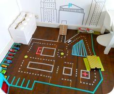 ¡pistas de carritos con cinta adhesiva! Es una de las mejores ideas para cuartos de juego infantiles que he visto recientemente y a partir de ella puedes crear infinidad de escenarios sin necesidad de tener un perol gigante metido en una caja.