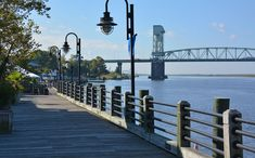 Wilmington's River Walk by the Cape Fear River Cape Fear, Wilmington Nc, River Walk, Walking By, Garden Bridge, North Carolina, Outdoor Structures, Travel, Projects