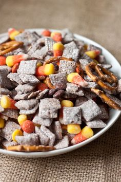 Use Chex, candy corn and M&Ms to make this muddy buddy mix. Easy halloween party food, halloween party ideas, #halloween #recipe