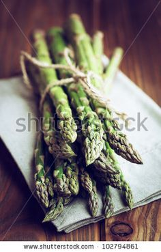 Green asparagus on a napkin and wooden table by B. and E. Dudzinscy, via Shutterstock
