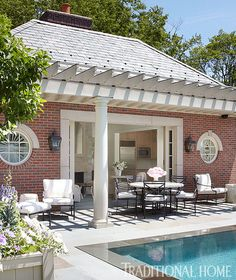 A shady pergola by a Hamptons pool is the perfect spot to have a long lunch or early evening glass of rosé as the sun sets | Traditional Home