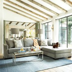 Sophisticated living room features a sloped ceiling accented with rustic wood beams placed over a gray couch with chaise lounge facing a gray cowhide bench doubling as a coffee table atop a sky blue rug.