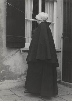 Vrouw in streekdracht uit Noordwijk aan Zee. De vrouw is gekleed in zondagse dracht en ze is in de rouw. Over de ondermuts en het oorijzer draagt ze een rouwmuts met fijngeplooide voorstrook en opgespelde punten. Het oorijzer heeft rechthoekige gouden 'boeken'. Achter de boeken is een paar mutsenspelden in de muts gestoken. De vrouw heeft een gevoerde cape omgeslagen. 1955 #ZuidHolland #Noordwijk