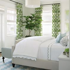 The color scheme of our Coronado Showhouse master bedroom is inspired by the green fig leaf-patterned drapes, which have robin's egg blue accents that are repeated in the chevron dhurrie rug, leather settee, and fringed accent pillow.