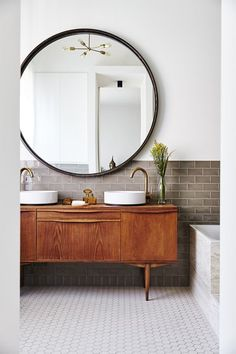 this is beautifully done. use mid century sideboard as vanity (make sure it's sealed), with simple top mounted basins, muted colours in the subway wall tiles and floor tiles, and cool oversized round mirror. Super-cool bathroom.