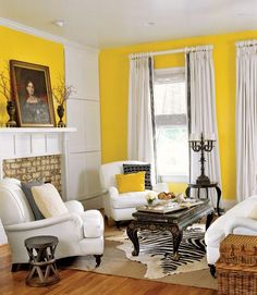 Less-Than-Mellow Yellow: Black and white furnishings with strong silhouettes lend the living room graphic vigor when set against Benjamin Moore's vibrant Fiesta Yellow on the walls. Additional antiques allow warmth to breathe into the room. To minimize clutter, cupboards that mimic paneling flank the fireplace. The chairs and sofa shown are by Williams-Sonoma Home.