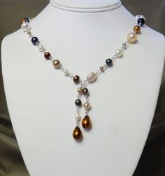 Julie's Pearl Necklace $125.00  These pearls that are taupe, brown, white, pinkish, grey, blue and copper and are not grouped in any shape or design.