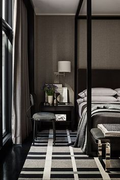 masculine bold color bedroom black canopy bed patterned black white grey carpet via Mark Cunningham Inc.