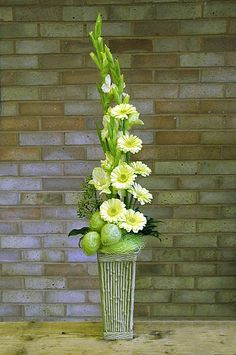"""Vertical style design - very slender triangle - three yellow Gladioli, seven yellow mini-Gerbera and hree fruits of Asclepias physocarpa """"Moby Dick"""" ~ Chrissie Harten"""